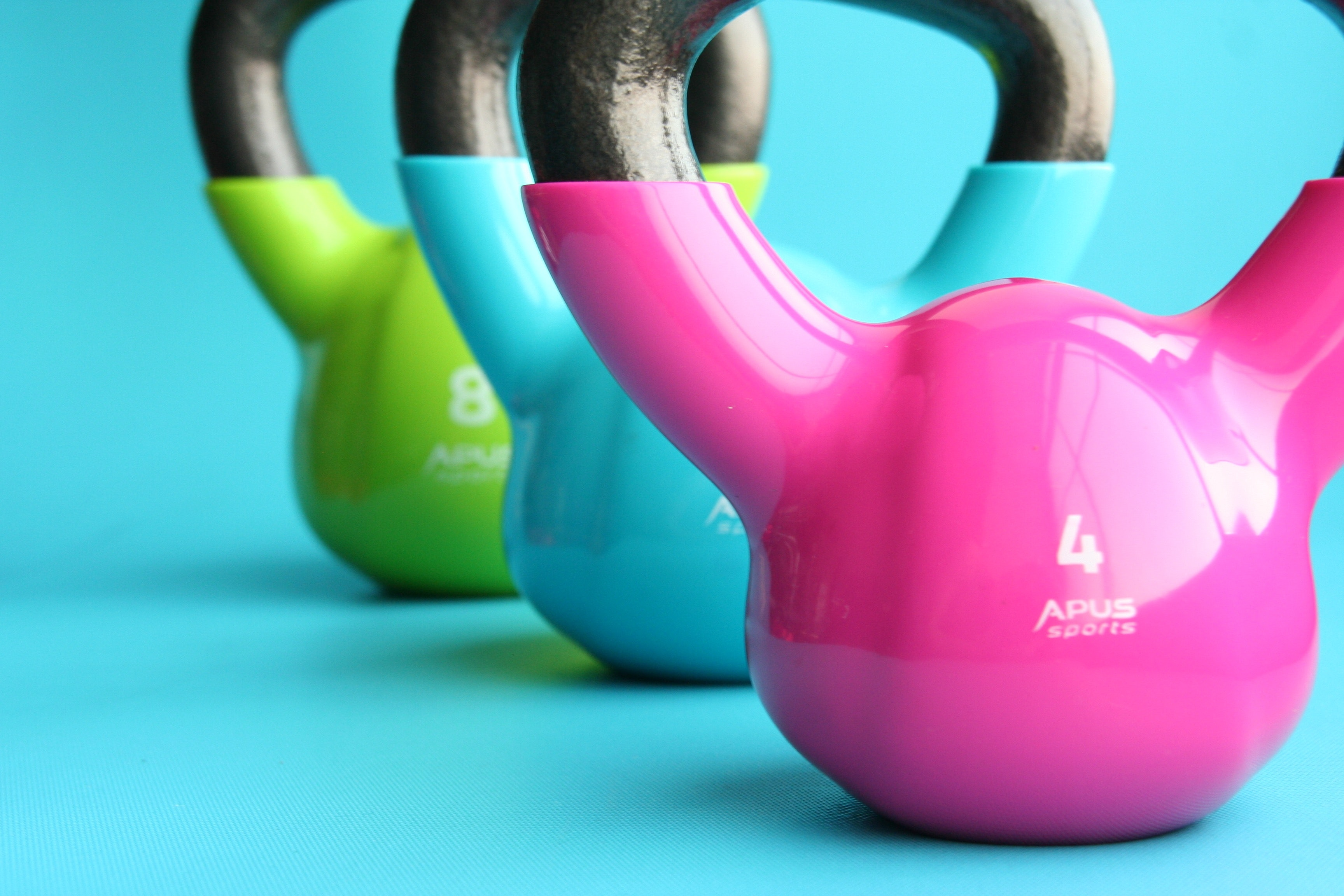 Pink, blue and green kettlebells on a blue surface
