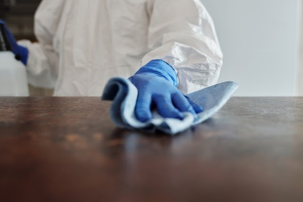a man cleaning a table with protective gear