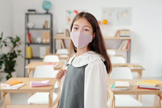 A girl back in school with a mask.