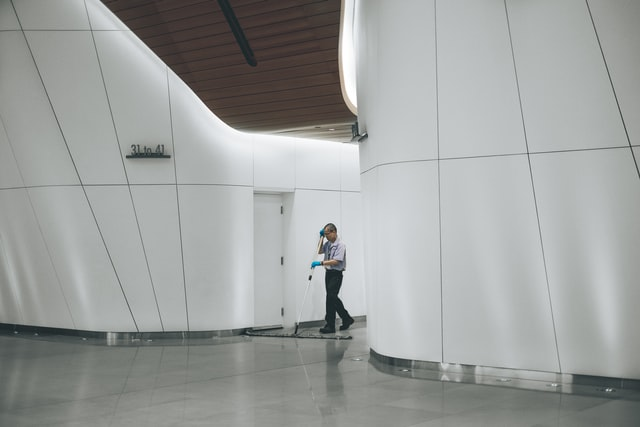 A janitor mopping the floor in a hallway